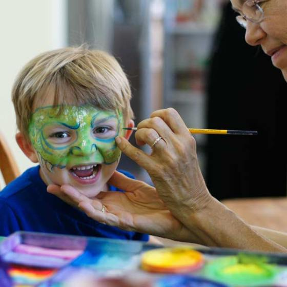Auntie Stacey face paints a dragon, face and body paint by Auntie Stacey Dennick, San Francisco Bay area face painter